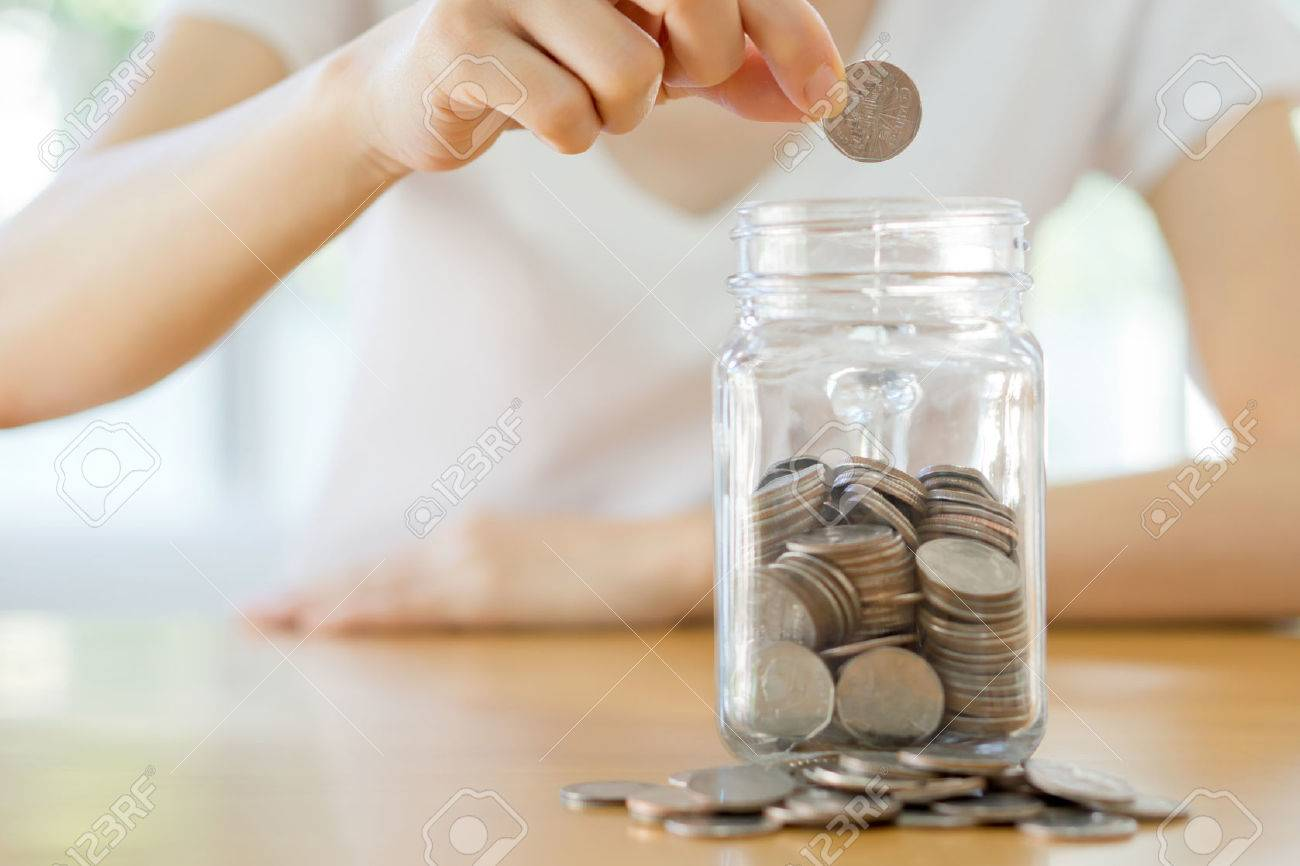 Woman hands with coins in glass jar, close up - 51186750