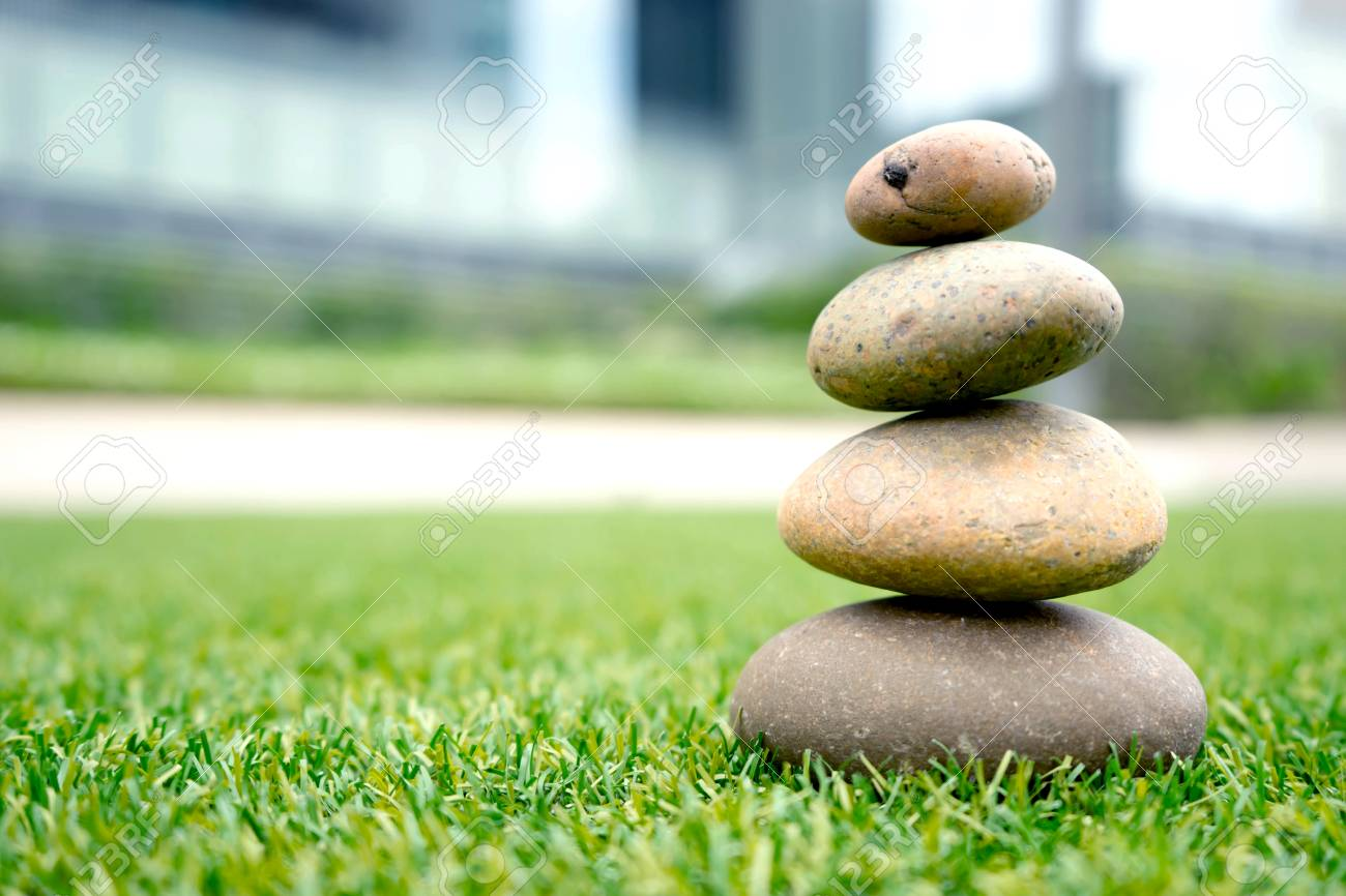 stones stacked up on grass - 83093483