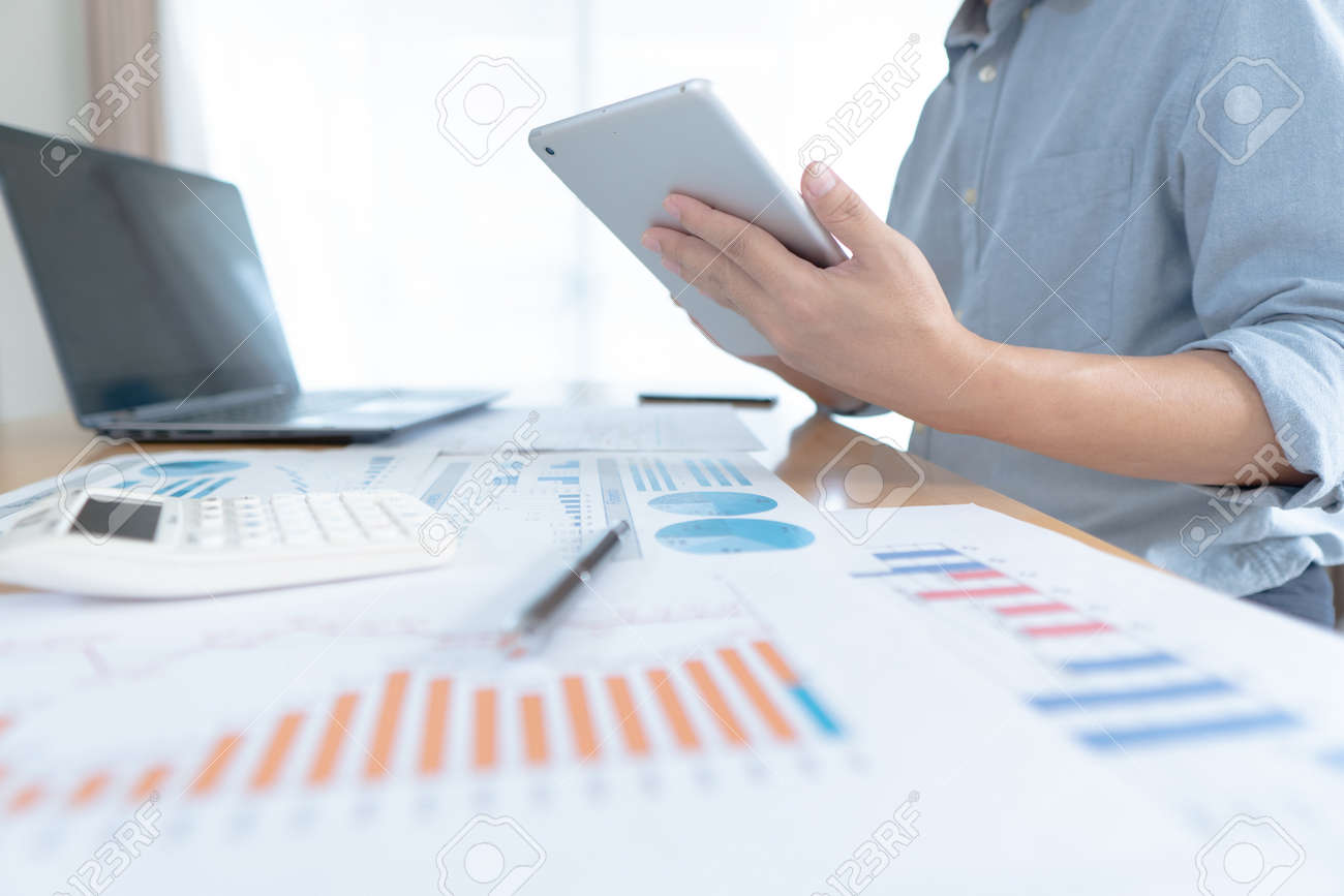 Businessman in casual wear stands beside desk to work at home with taplat. work from home concept. - 168839085