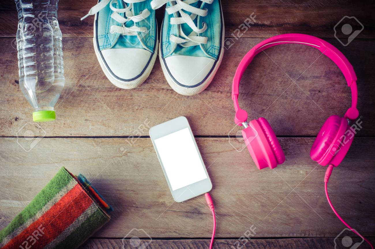 Shoes, water bottles headset smart phone scarf on a wooden table ready to depart. - 46154824