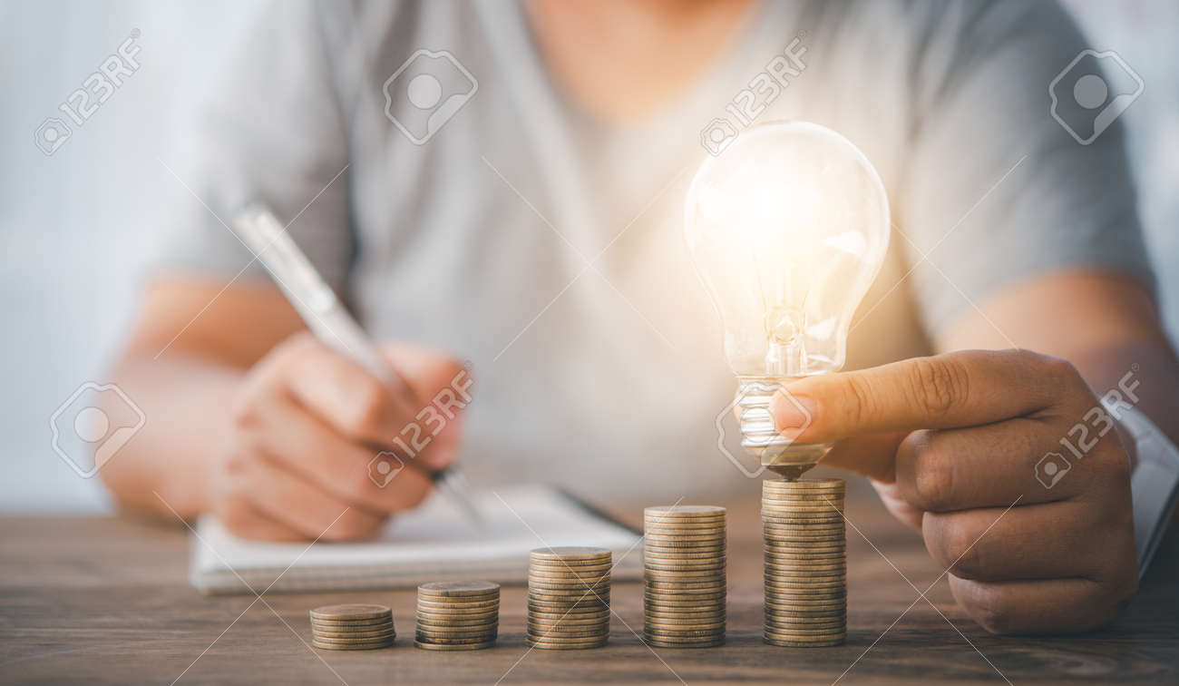 woman's hand holding a light bulb on a coin lying on a desk.Energy saving ideas to cut home expenses. - 163301659