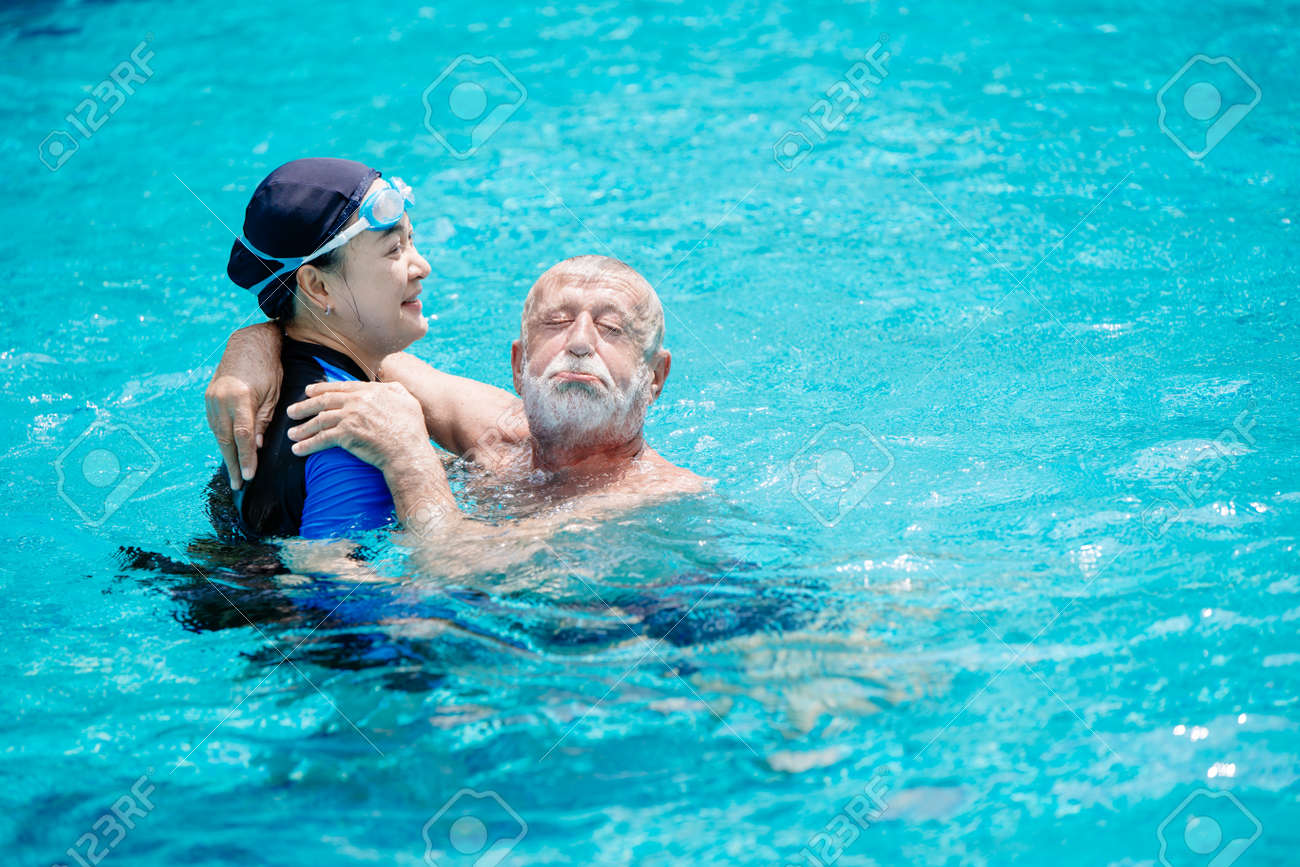Woman Teacher Help To Training Support Elder Man Swimming At Stock Photo Picture And Royalty Free Image Image 156104287