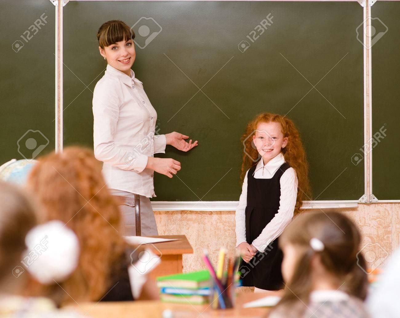 Schoolgirl And Teacher Near A School Board Stock Photo 22449928