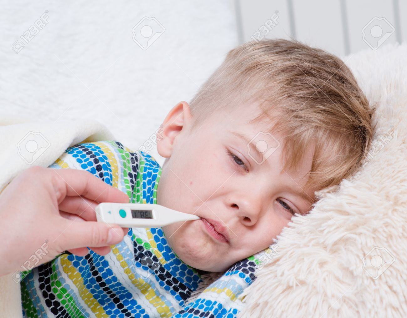 Sick kid with high fever laying in bed and mother taking temperature sick kid with high fever laying in bed and mother taking temperature stock photo altavistaventures Choice Image