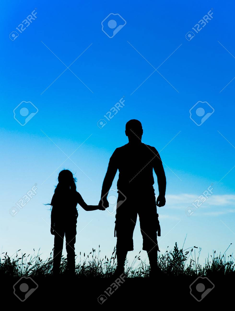 Silhouette Father And Daughter Holding Hands At Sunset Stock Photo