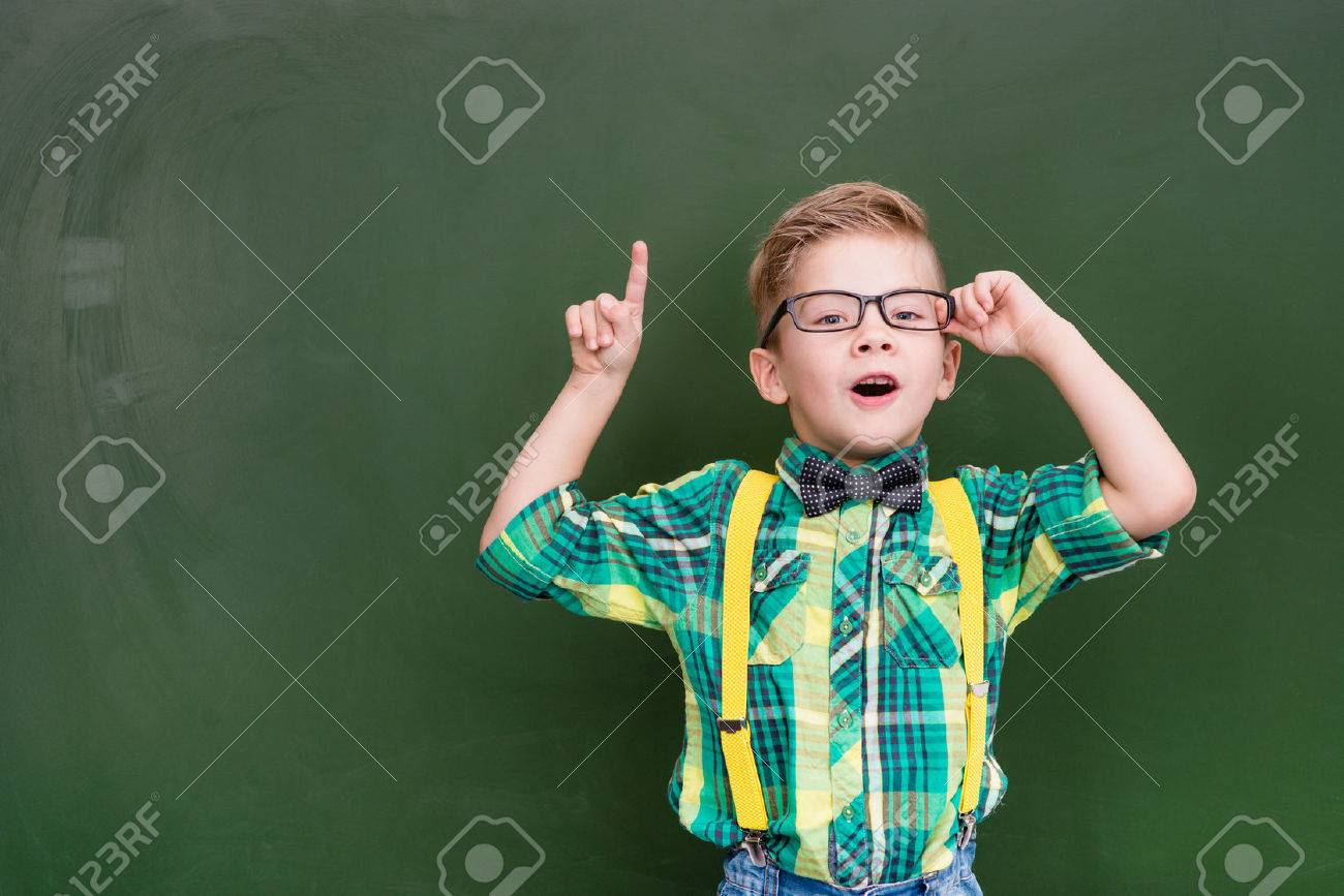 Surprised boy stands near empty chalkboard and showing finger up. - 51089497