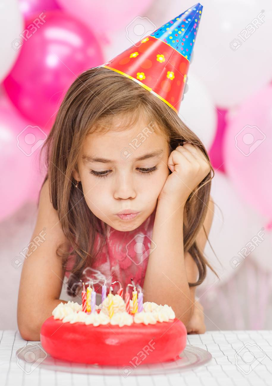 Little Girl In Party Hat Blowing Candles On Cake Stock Photo