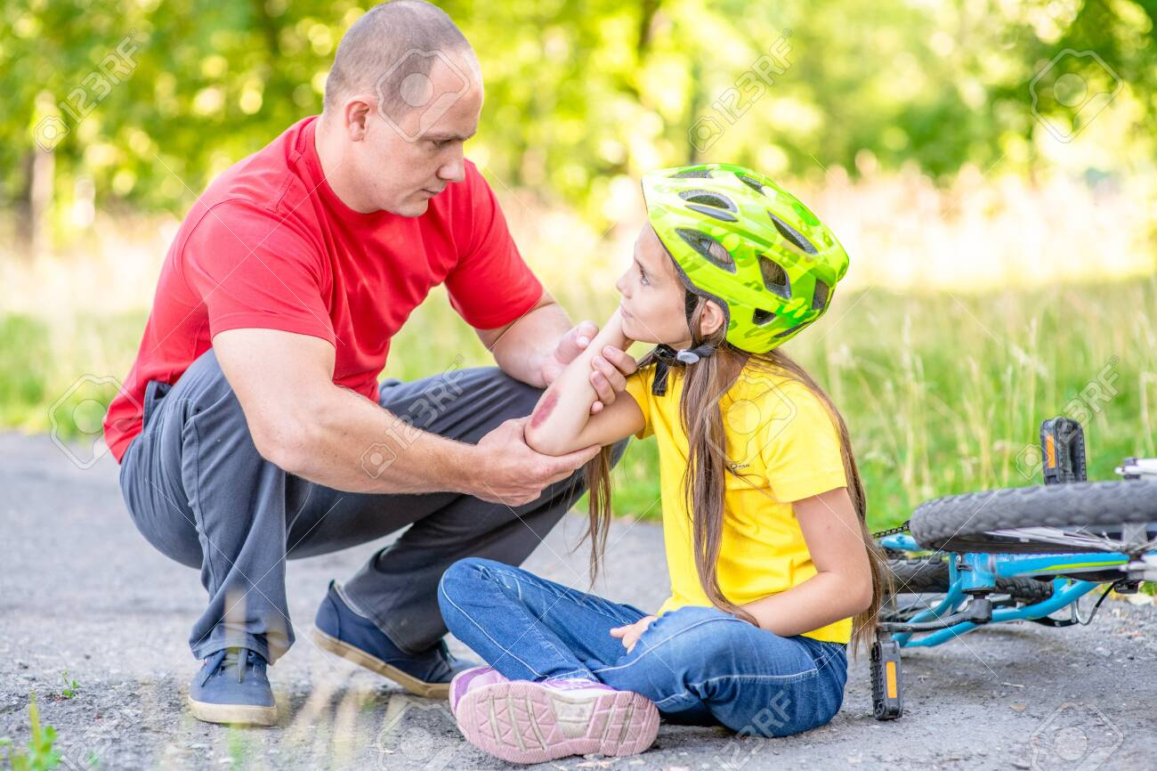 Father looks at the wound of his daughter, who fell from a bicycle. - 140864540