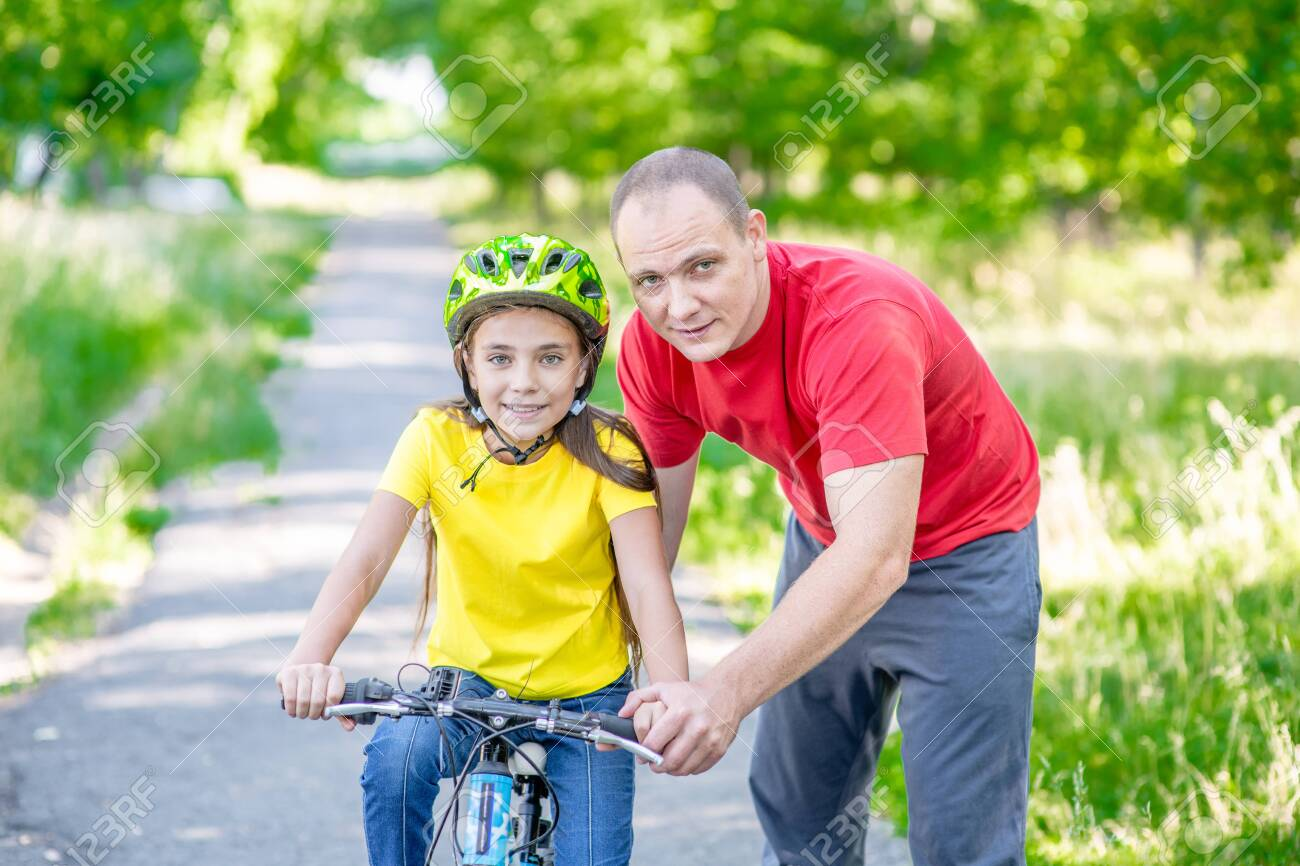 Happy family. Father teaches his daughter to ride a bicycle in the summer park. - 140873082
