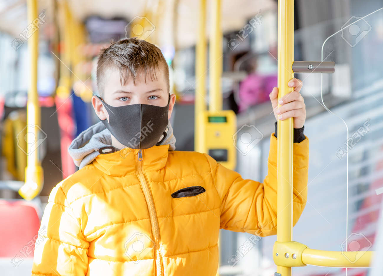 Young boy wearing protective mask holding on to the handrail in the bus. - 165494698