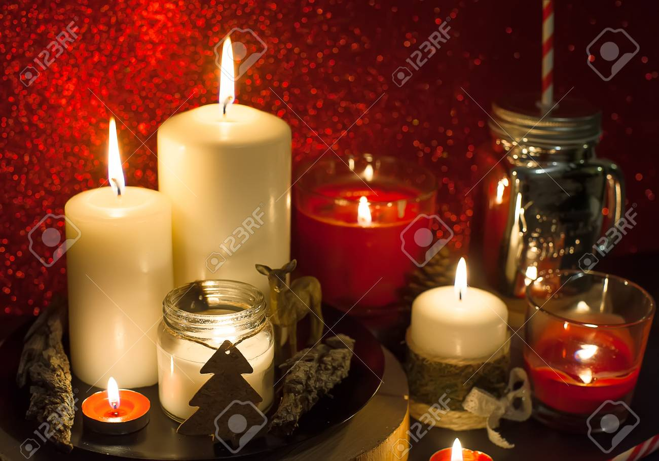 Christmas Candles And Holiday Decorations On Red Blurred Abstract