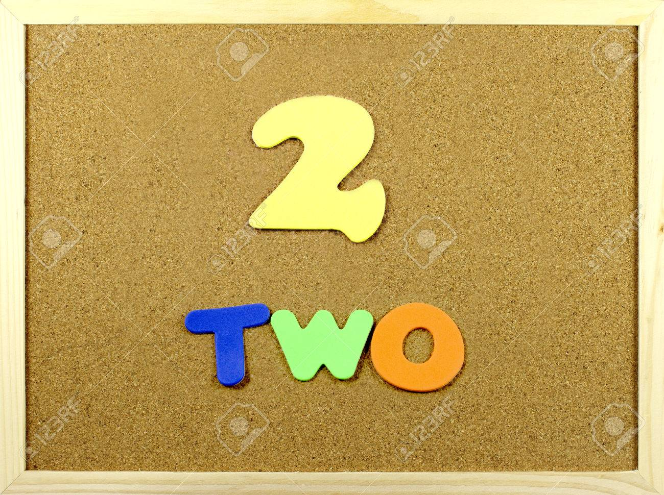 corkboard with the word and number two written with colorful letters stock photo 30938045