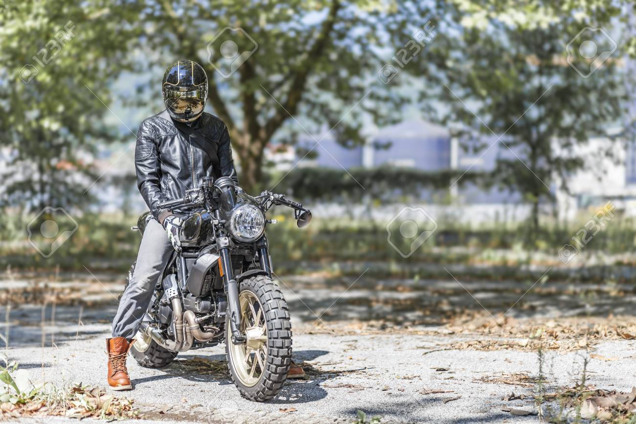 Cool Looking Motorcycle Rider On Custom Made Scrambler Style Cafe Racer In The Park Stock Photo