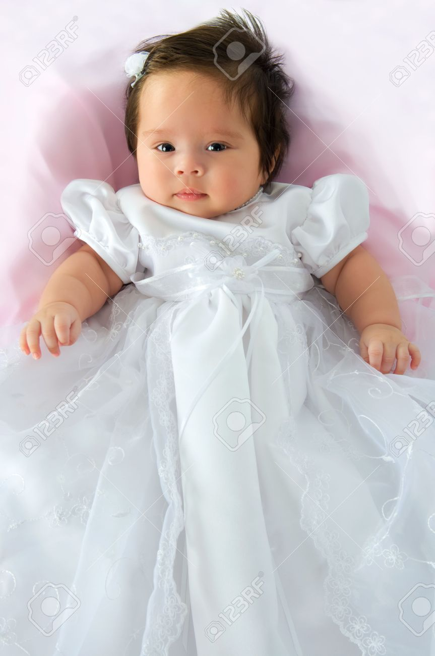 9ef389e926348 Newborn baby girl in a white baptism dress on a pink blanket