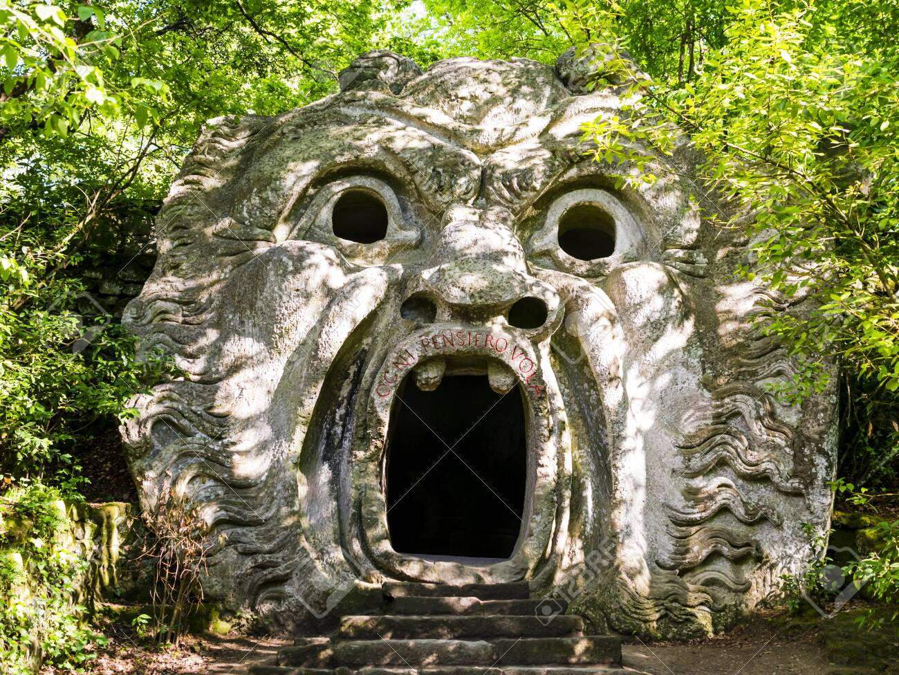 Stunning view of Orcus Mouth, a grotesque sculpture at famous Park of the Monsters, also named Sacred Grove, Bomarzo Gardens, province of Viterbo, Lazio, Italy - 150525780
