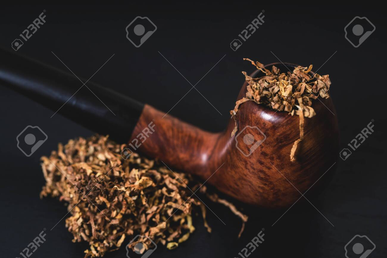 smoking pipe with tobacco on a black background - 135038432