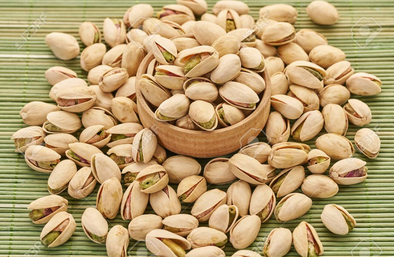 fresh pistachios close-up on a green wooden background - 142219561