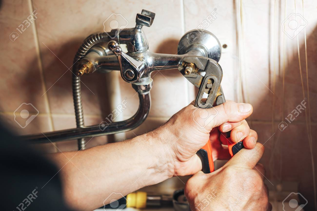 Man Repair And Fixing Leaky Faucet In Bathroom Stock Photo, Picture ...