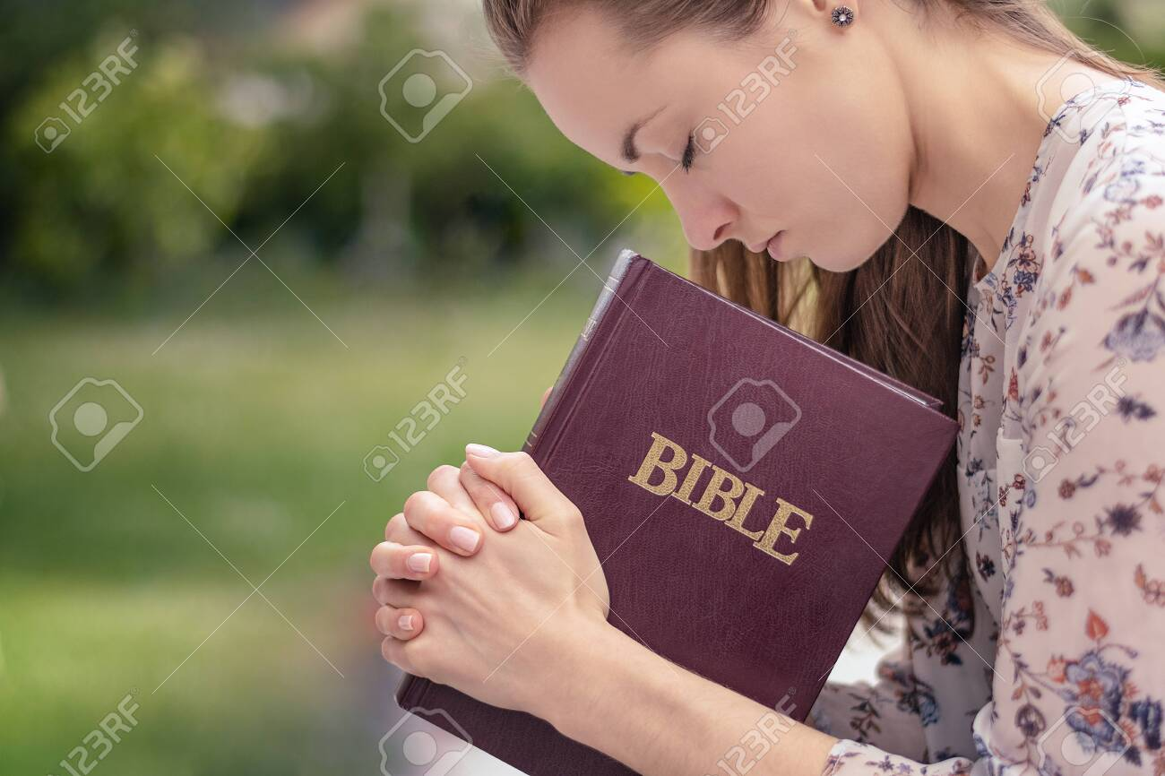 Christian worship and praise. A young woman is praying and worshiping in the evening. - 129575865