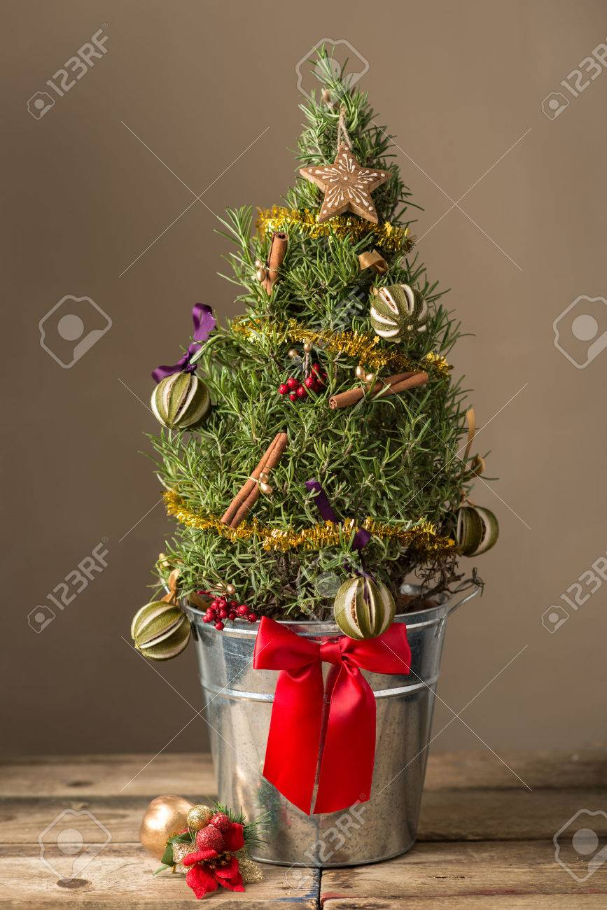 miniature christmas tree in a silver pot with a red bow and decorations stock photo
