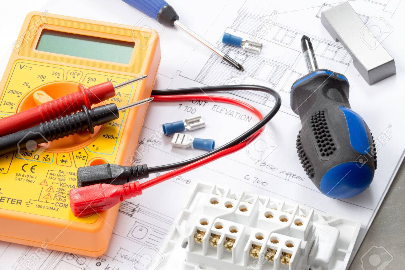 Yellow Electrical Multimeter On House Plans With A Blue Screwdriver ...
