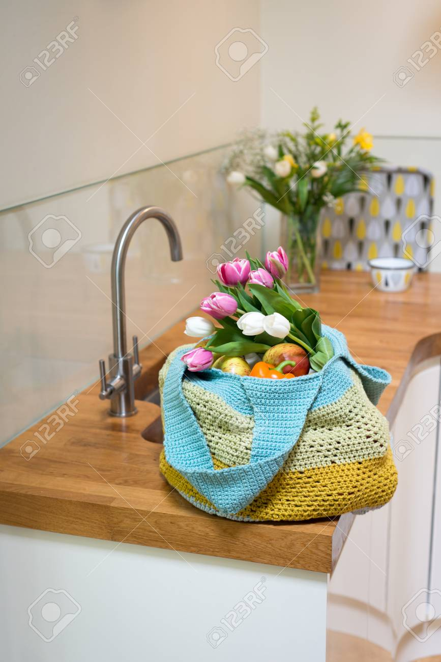 Fruits Vegetables And Fresh Flowers In A Crocheted Bag On A