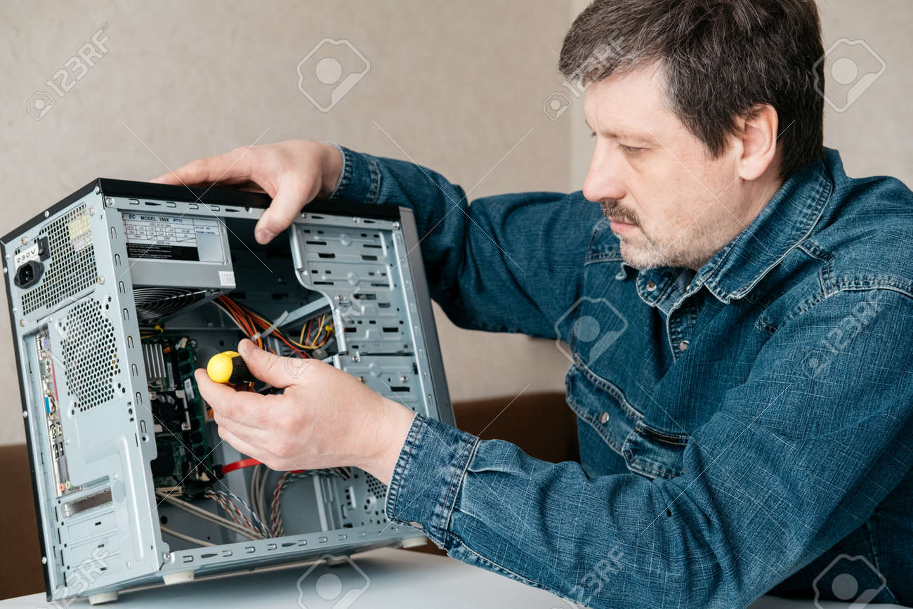 Computer technician engineer with screwdriver in his hand is repairing the personal computer. Concept of computer hardware, repairing, upgrade and technology. - 159180437