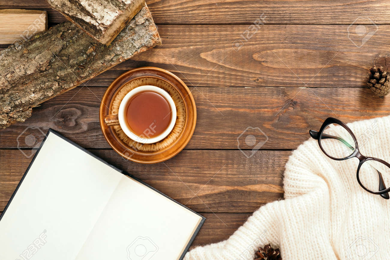 Hygge style flatlay composition with cup of tea, book with empty pages, white knitted scarf, woman glasses, firewood on wooden desk table. Autumn or winter holidays concept. Flat lay, top view. - 159305566