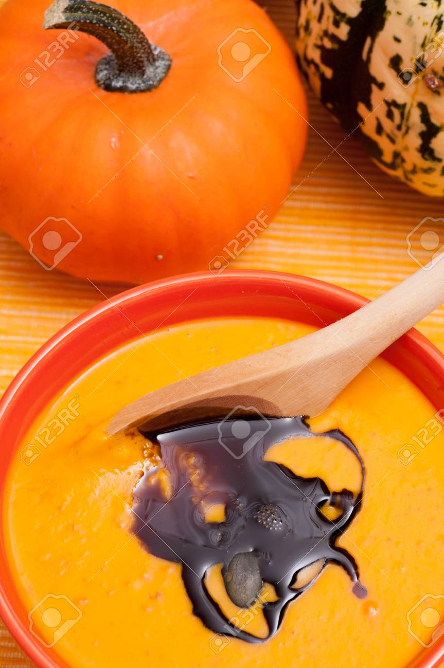 Pumpkin soup with oil and a wooden spoon Stock Photo - 15111721