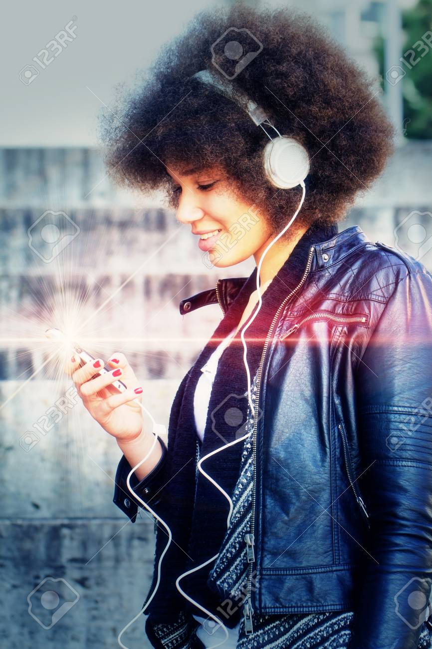 Girl with headphones in the city - photo with light effect - 34704192