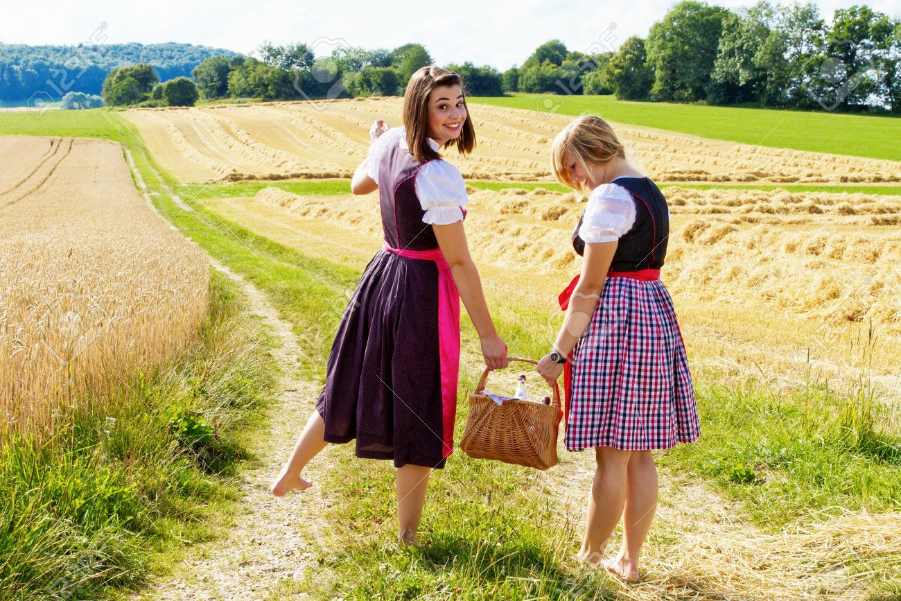 https://previews.123rf.com/images/photojog/photojog1411/photojog141100970/33768430-Tow-girls-in-dirndl-walking-with-a-picnic-basket-Stock-Photo-barefoot.jpg