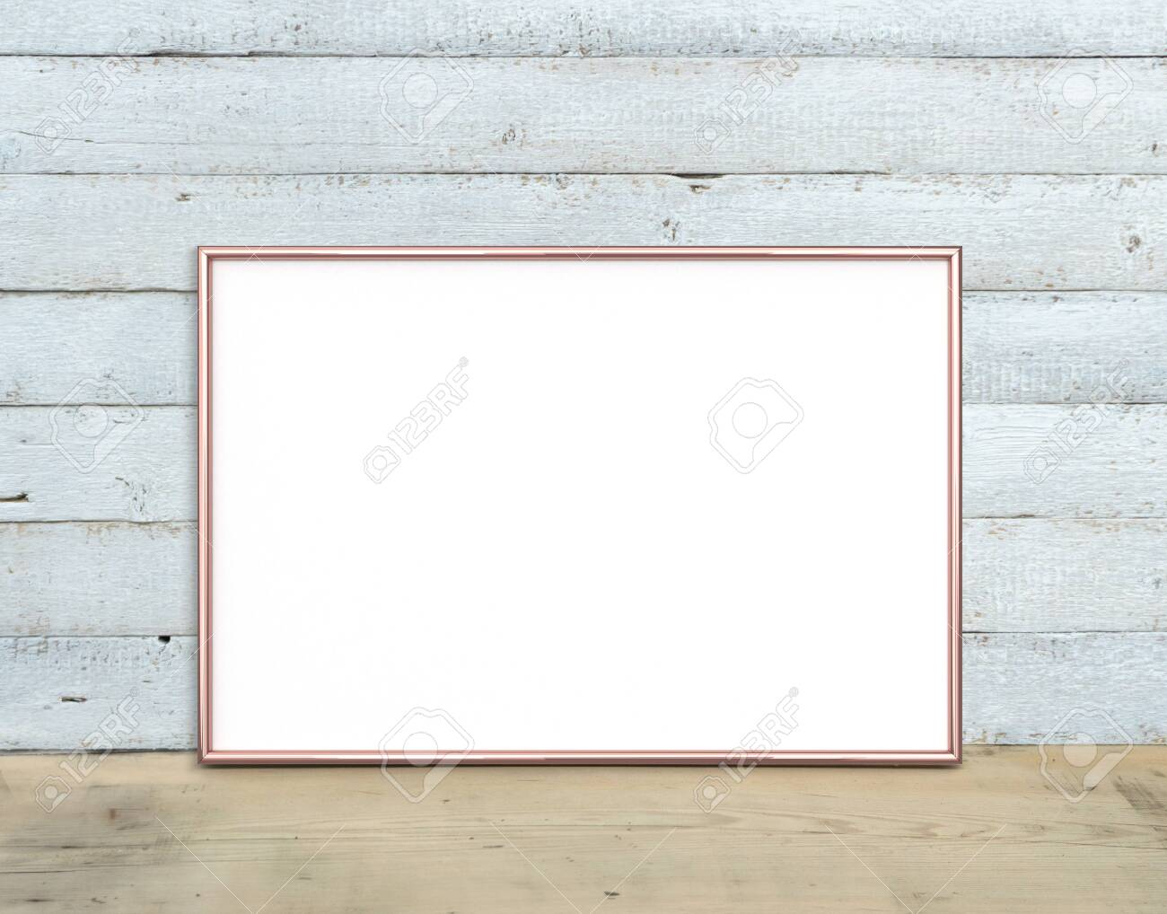 Rose Gold A4 horizontal Frame mockup stands on a wooden table on a painted white wooden background. Rustic style, simple beauty. 3 render. - 125702711