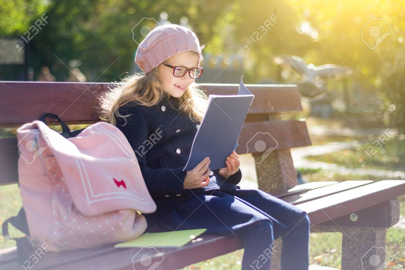 Little girl elementary school student sitting on bench with backpack,