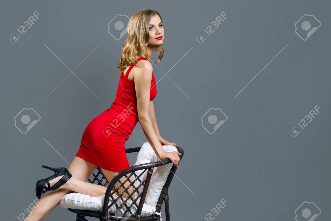 Fashionable young blonde girl in red dress on gray - 100228312