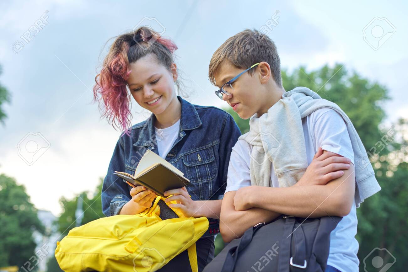 Outdoor portrait of two talking teenagers, students boy and girl with notepad, back to school - 146515832