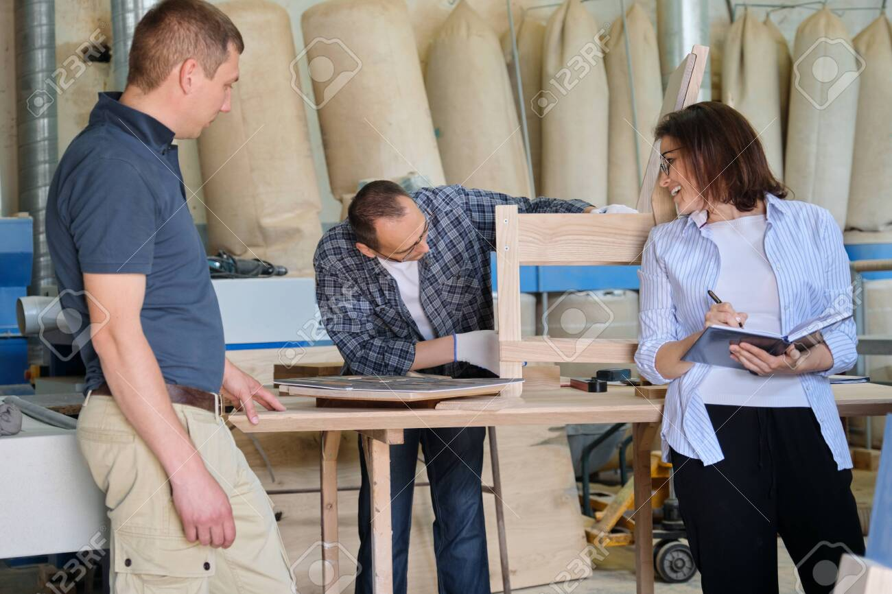 People working in carpentry workshop, woman and men workers making sample of wooden chair using design drawing - 149148023