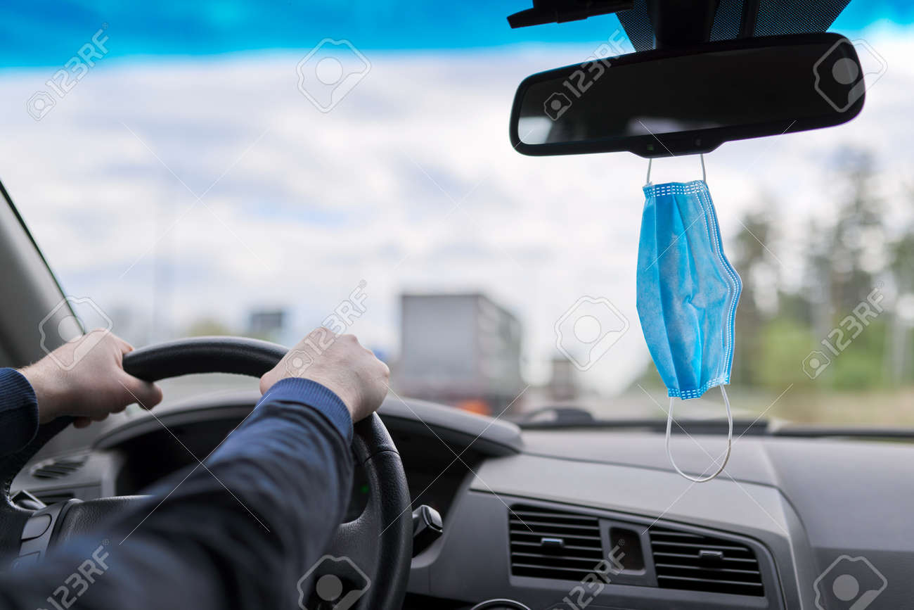 Protective medical mask of the driver in the car, man's hands on the steering wheel of moving vehicle - 155423815