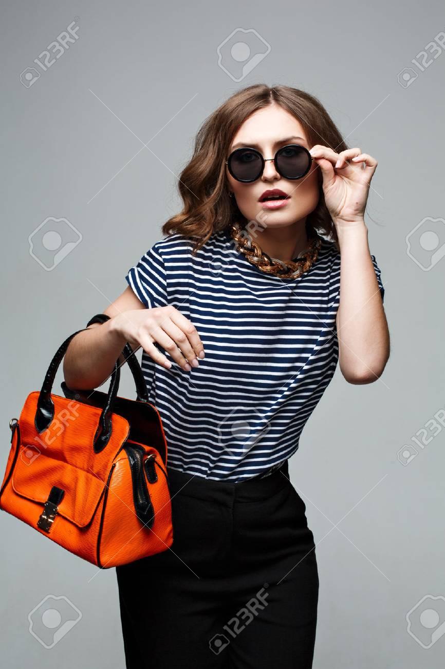 woman hands holding orange bag. Street look. Fashion look. Street..
