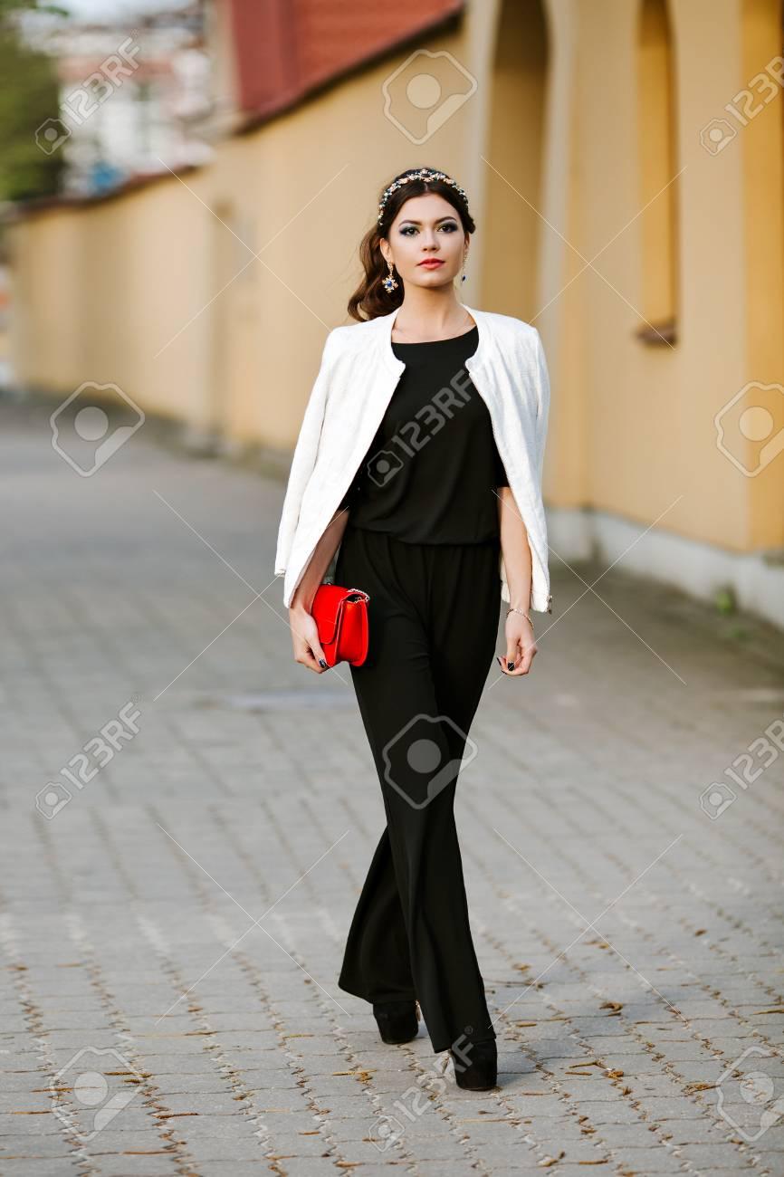sports shoes 0775c 44636 Giovane donna alla moda va in città con un sacchetto alla moda rosso. Sulla  spalla della borsa ragazza, vestito con un abito pantalone nero, giacca ...