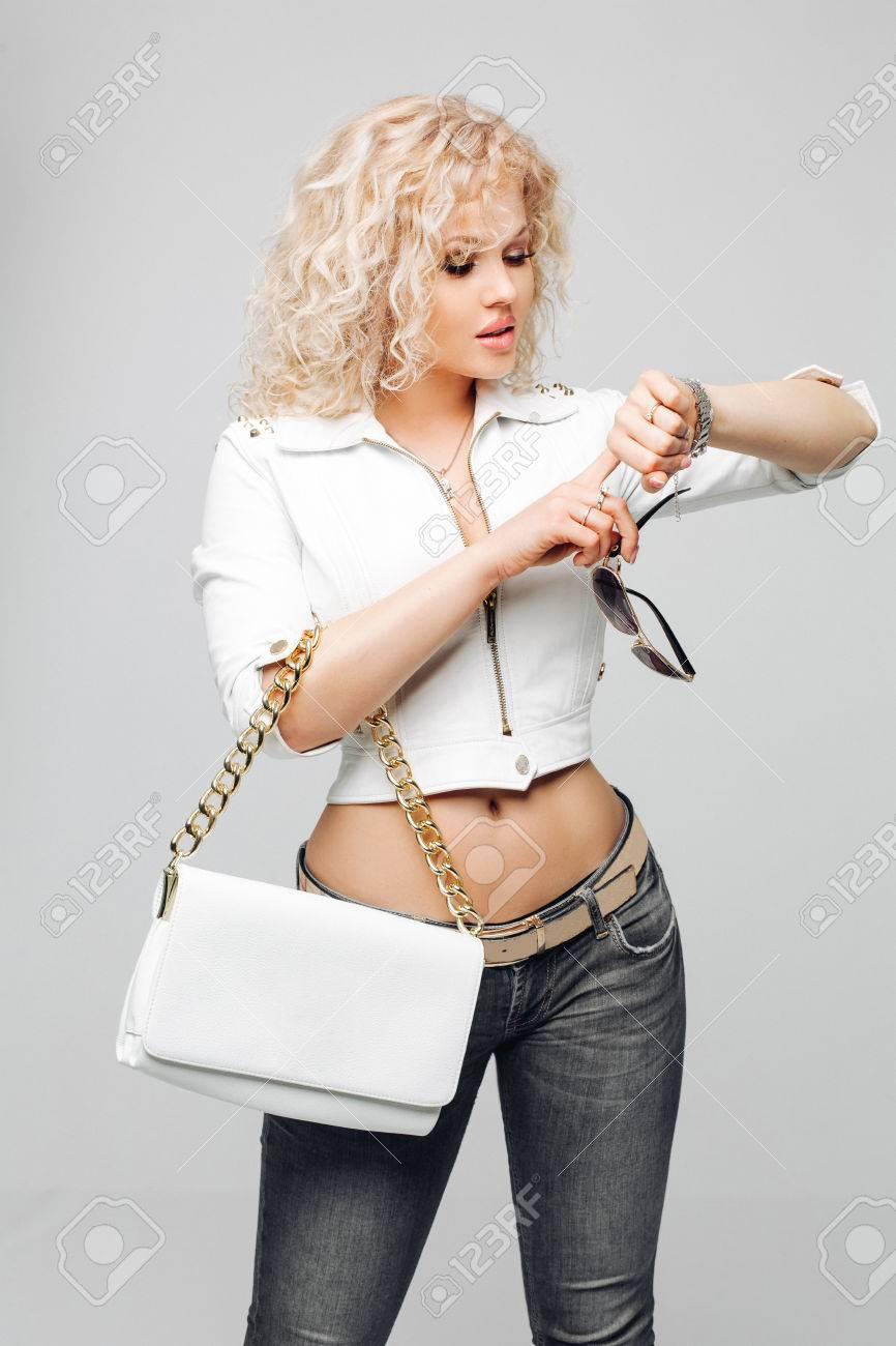 grande variété de modèles nouveaux styles prix bas Portrait de blonds bouclés dans une veste blanche de veste en cuir, un jean  bleu, miroir des lunettes de soleil, tenant un sac en cuir blanc, regarde  ...