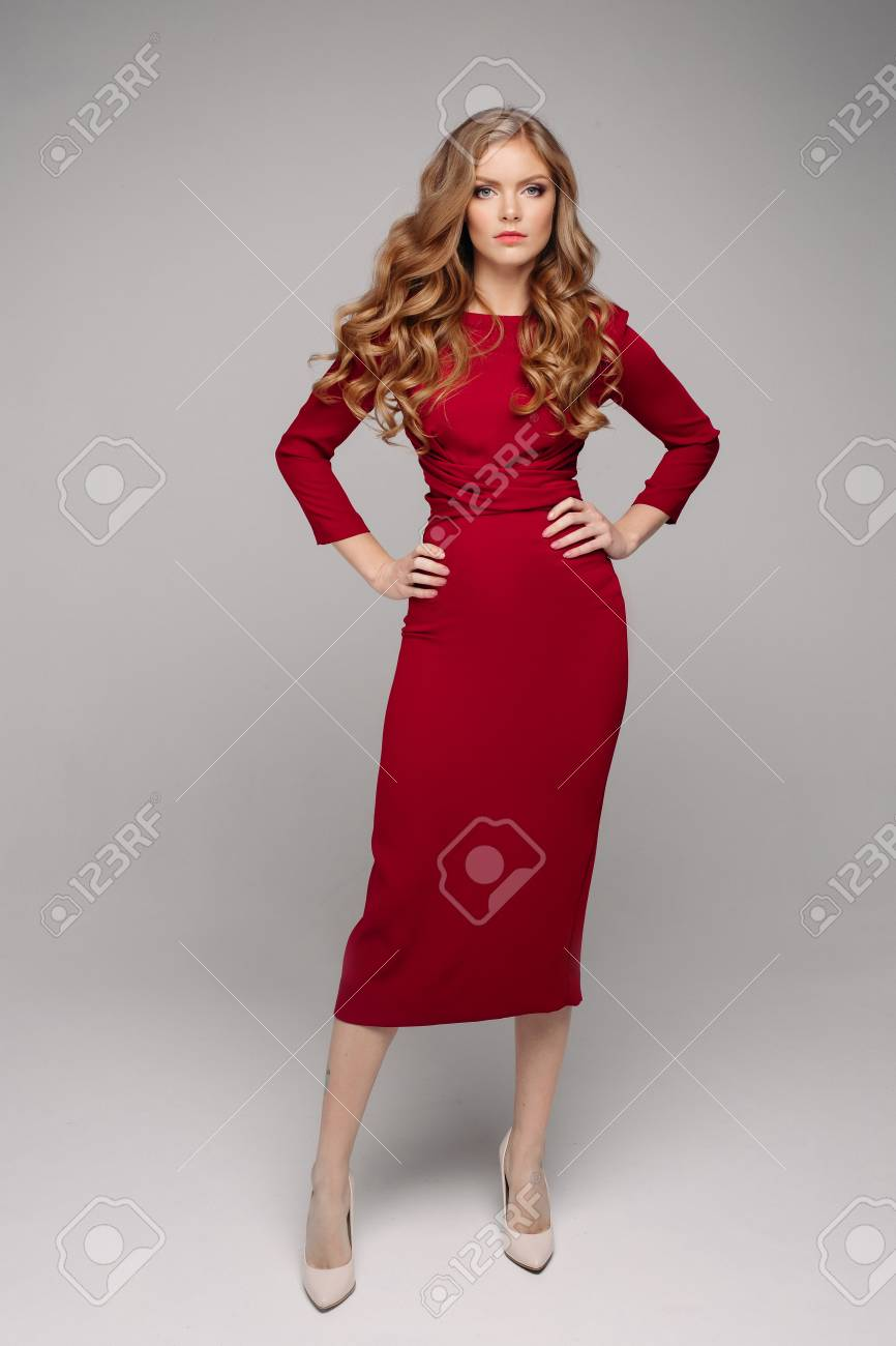 Gorgeous young woman in elegant evening red dress and beige heels. - 113825156