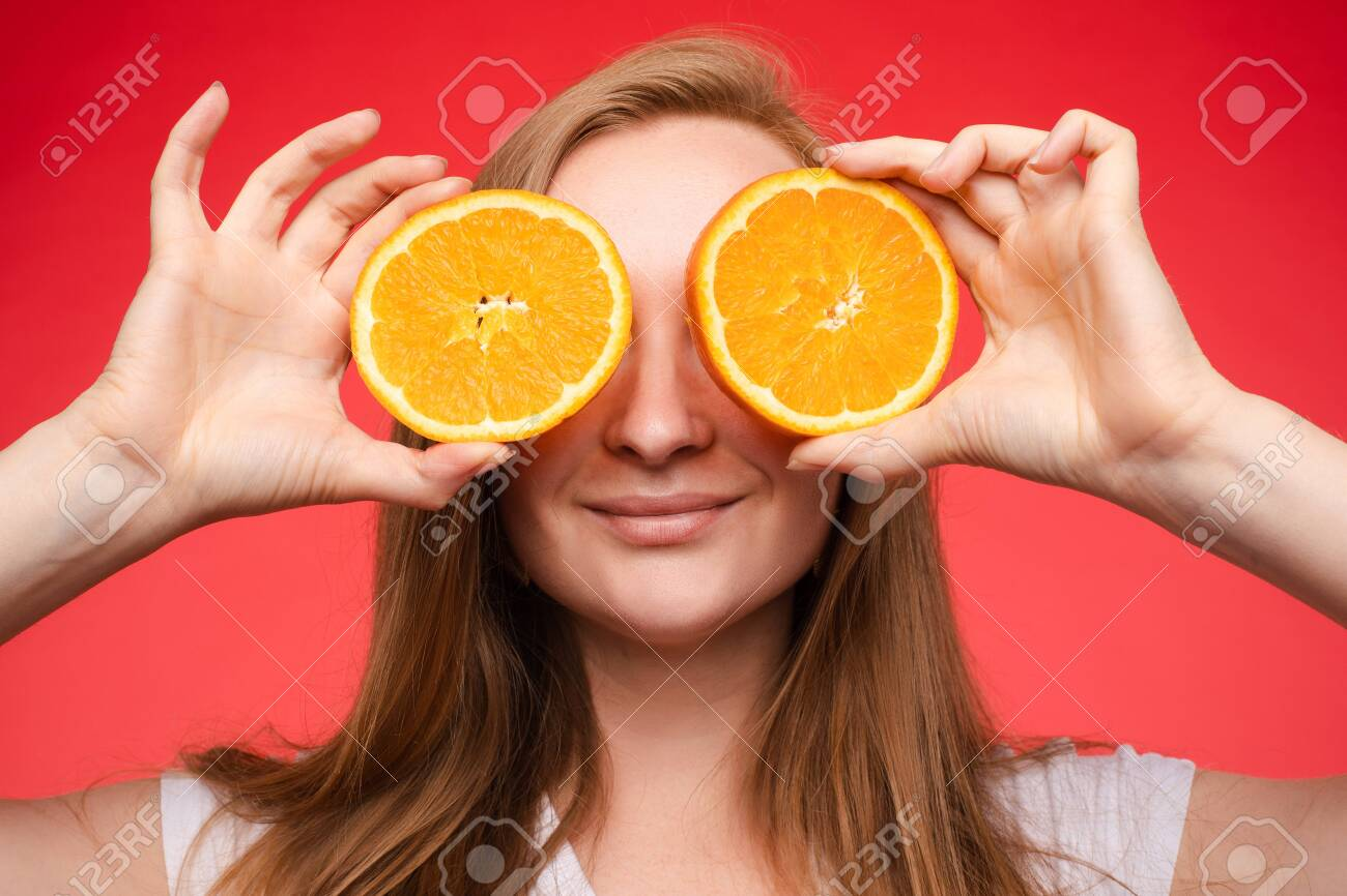 Funny fashionable girl with hairstyle holding oranges on eyes. - 147862303