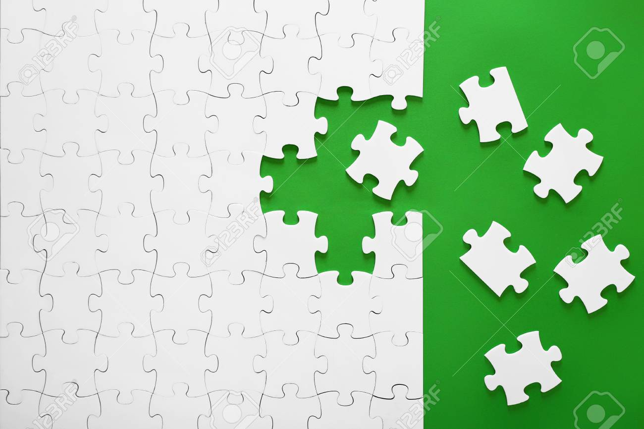 White puzzles on a green background. The puzzle pieces are put together. The header, the template for a business idea. Teamwork in the organization. - 111286177