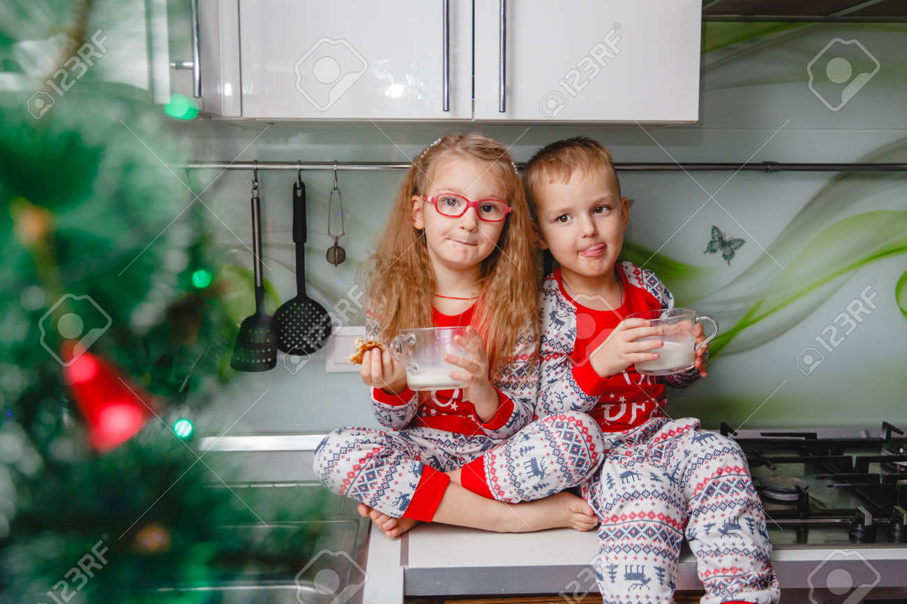 Little brother and sister sit on a Christmas-decorated kitchen table in pajamas and drink milk. Girl with glasses - 159148180