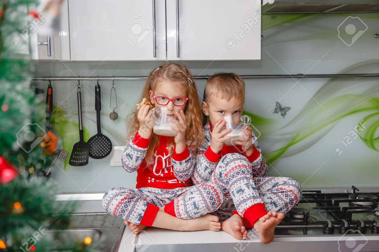 Little brother and sister sit on a Christmas-decorated kitchen table in pajamas and drink milk. Girl with glasses - 159146734