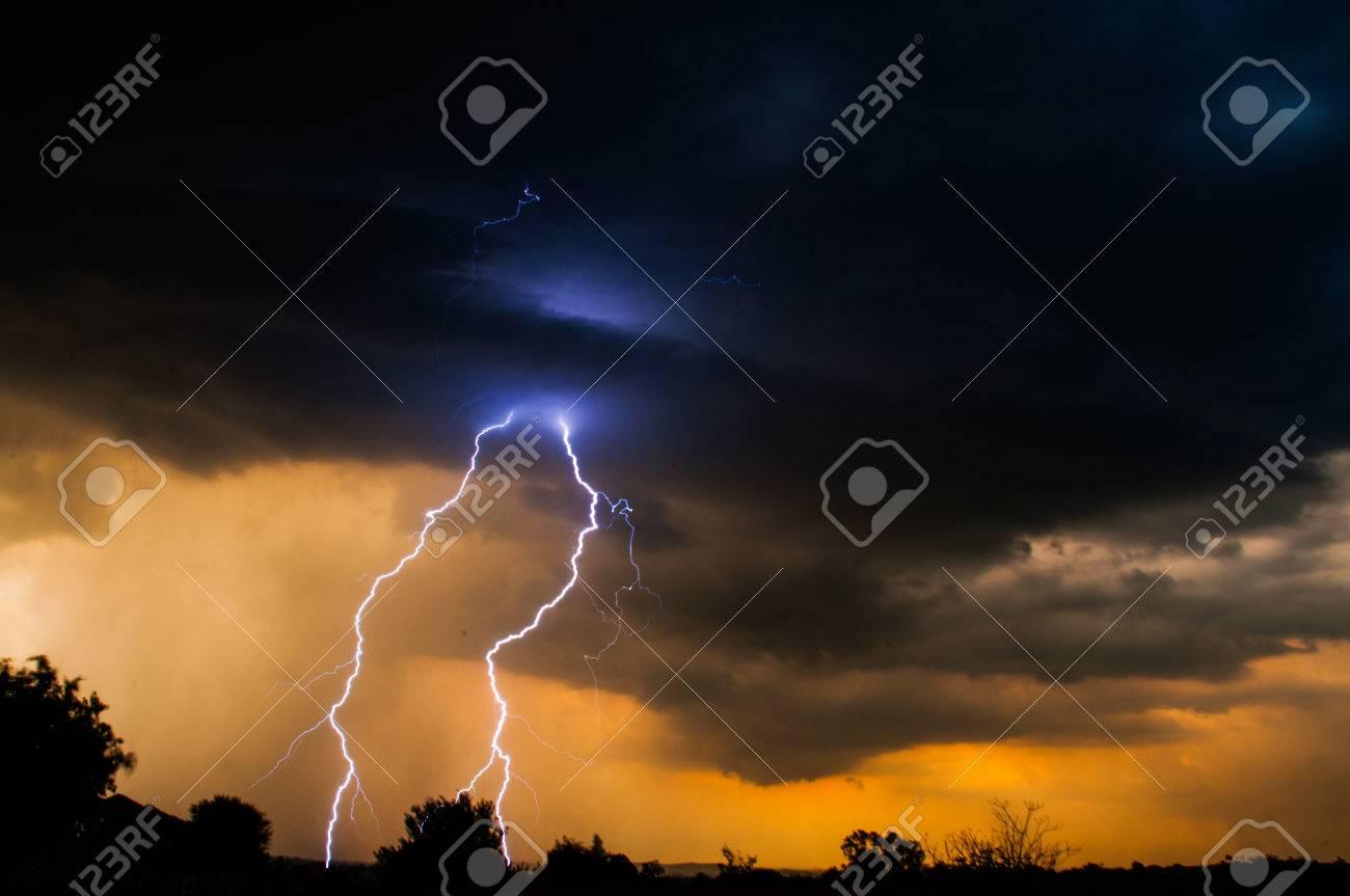 Sun setting on horizon with cloud to ground lightning Stock Photo - 46910555