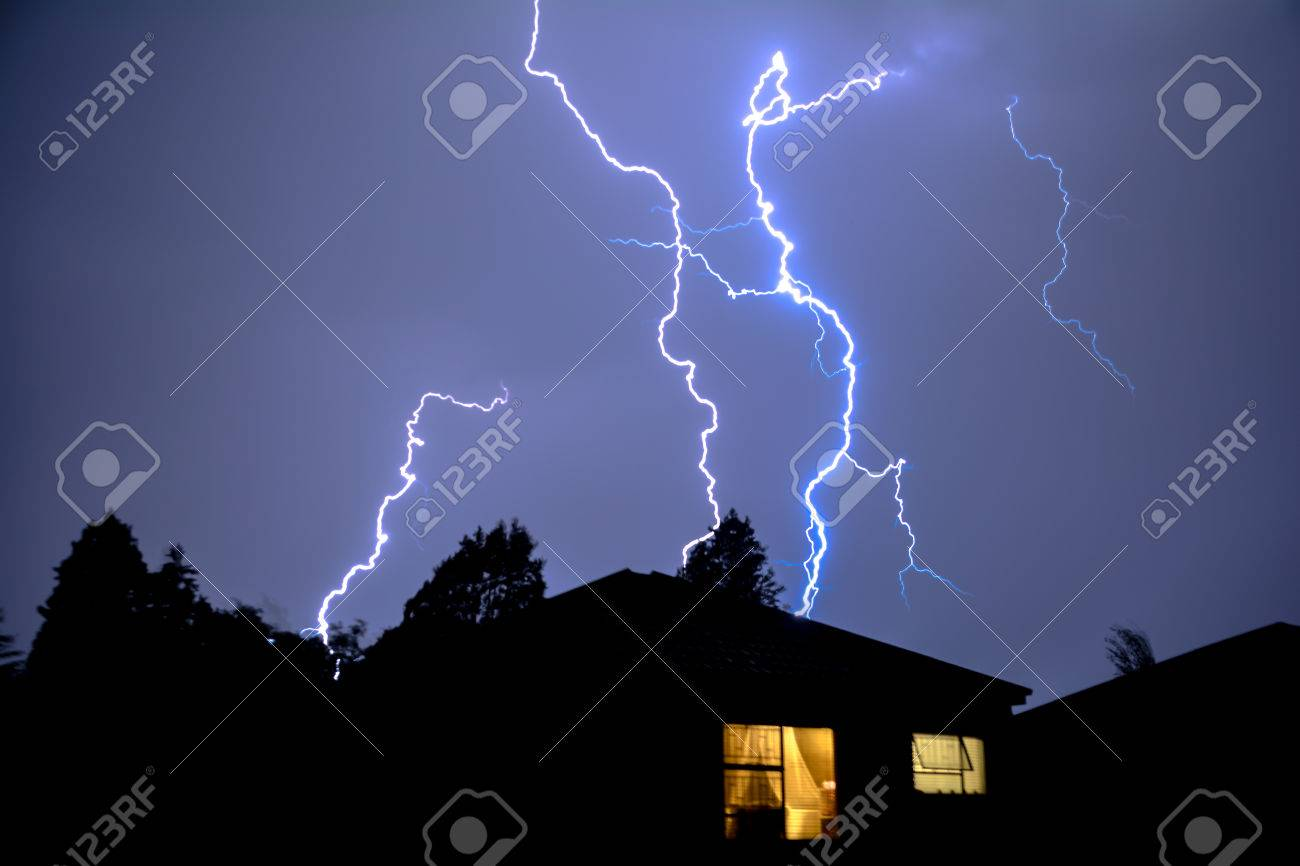 Cloud to Ground Electric Lightning behind house roof tops Stock Photo - 54312164