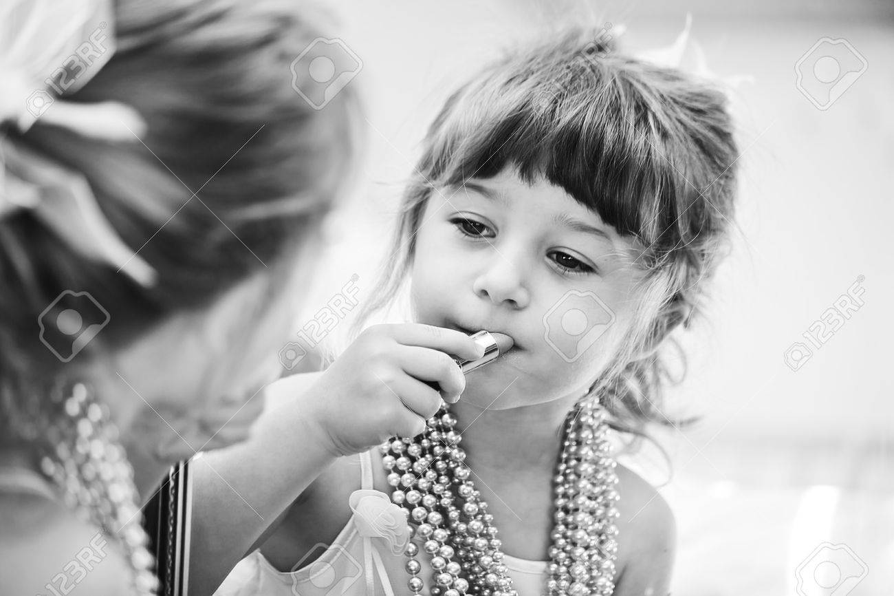 little girl putting on lipstick in front of the mirror - 9179750