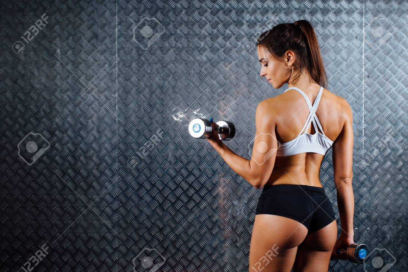 Attractive Fitness Woman With Dumbbell Indoor Portrait Trained