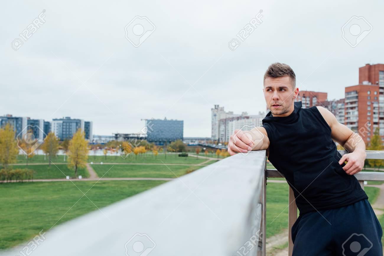 2d49951a883 Homem Da Aptidão Do Esporte Que Levanta Contra O Contexto Da Cidade. Atleta  Masculino Fora Do Parque Da Queda. Ajuste O Modelo Masculino Da Aptidão Na  Roupa ...